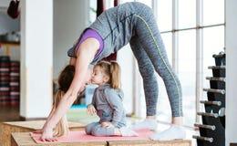 La maman et la fille exécutent ensemble différents exercices Image libre de droits