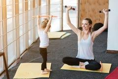 La maman et la fille exécutent ensemble différents exercices Photos stock