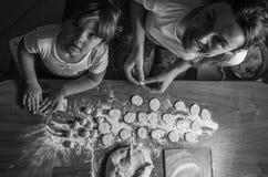 La maman et la fille fabriquent la farine à partir de la farine pour faire cuire des boulettes images libres de droits