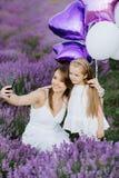 La maman et la fille font le selfie sur le smartphone dans le domaine de lavande Concept d'amour de famille Photo stock
