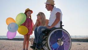 La maman et la fille heureuses tiennent le papa proche handicapé dans le contre-jour, la famille parlent de la grossesse, les par banque de vidéos