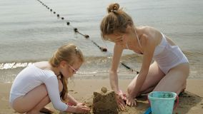 La maman et la fille jouent sur la plage, construisant un château de sable Jour ensoleill? d'?t? Vacances clips vidéos