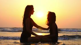 La maman et la fille méditent ensemble sur l'océan au beau coucher du soleil banque de vidéos