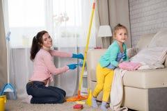 La maman et la fille nettoient dans l'appartement photos stock