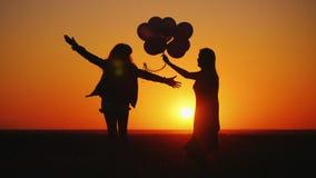 La maman et la fille ont l'amusement au coucher du soleil, dansent et tiennent des ballons images libres de droits