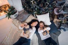 La maman et la fille rencontrent Noël heureux, la famille dans une chambre avec l'arbre de sapin de Noël et les cadeaux Vue supér Images stock