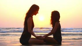 La maman et la fille s'asseyent ensemble sur la plage avec des mains de participation au coucher du soleil clips vidéos