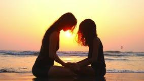 La maman et la fille s'asseyent ensemble sur la plage avec des mains de participation au coucher du soleil banque de vidéos