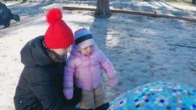La maman et la fille se sont tapies près des installation-oeufs sur le terrain de jeu en parc avec les pins grands en premier res banque de vidéos