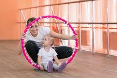 La maman et la fille sont engagées dans les sports avec un cercle Photographie stock
