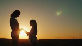 La maman et la fille tiennent des mains, regardent l'un l'autre Silhouettes au coucher du soleil images libres de droits