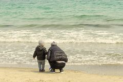 La maman et l'enfant sur le bord de la mer rassemblent des coquilles image libre de droits