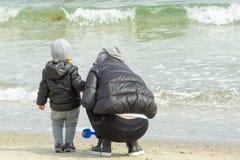 La maman et l'enfant sur le bord de la mer rassemblent des coquilles Plan rapproch? photos stock