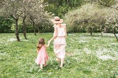 La maman et la fille marchent dans le jardin Images stock