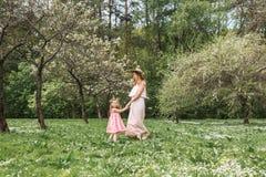 La maman et la fille marchent dans le jardin Photo libre de droits