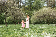 La maman et la fille marchent dans le jardin Photo stock