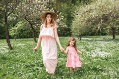 La maman et la fille marchent dans le jardin Images libres de droits