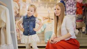 La maman et la fille regardent eux-mêmes dans le miroir dans un magasin d'habillement du ` s d'enfants photographie stock libre de droits
