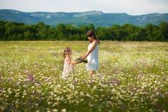 La maman et la fille sur un pique-nique dans la camomille mettent en place Deux belles blondes dans la camomille mettent en place Photo stock