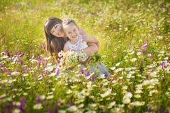 La maman et la fille sur un pique-nique dans la camomille mettent en place Deux belles blondes dans la camomille mettent en place Images libres de droits