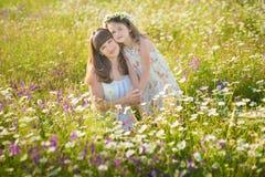 La maman et la fille sur un pique-nique dans la camomille mettent en place Deux belles blondes dans la camomille mettent en place Image stock