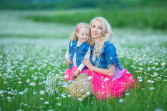 La maman et la fille sur un pique-nique dans la camomille mettent en place Deux belles blondes portant la veste de jeans et le gi Photographie stock
