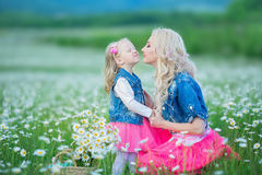 La maman et la fille sur un pique-nique dans la camomille mettent en place Deux belles blondes portant la veste de jeans et le gi Image libre de droits