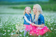 La maman et la fille sur un pique-nique dans la camomille mettent en place Deux belles blondes portant la veste de jeans et le gi Image stock
