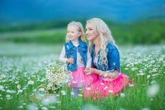 La maman et la fille sur un pique-nique dans la camomille mettent en place Deux belles blondes portant la veste de jeans et le gi Images libres de droits