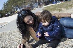 La maman et la petite fille mignonne jouant au lac échouent photos stock