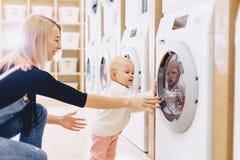 La maman et le bébé dans la blanchisserie prennent des choses et jouent image stock