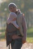 La maman et le bébé dans une bride se réjouissent les feuilles d'automne en baisse Image stock
