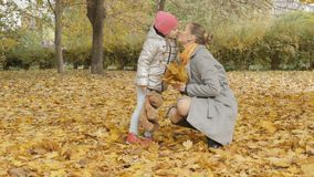 La maman et le bébé rassemblent les feuilles tombées par jaune en parc Photos stock