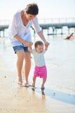 La maman et le bébé sur la plage ont l'amusement Photos stock