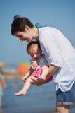La maman et le bébé sur la plage ont l'amusement Photo stock