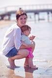 La maman et le bébé sur la plage ont l'amusement Photos libres de droits