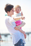 La maman et le bébé sur la plage ont l'amusement Images stock