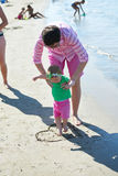 La maman et le bébé sur la plage ont l'amusement Image stock