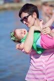 La maman et le bébé sur la plage ont l'amusement Image libre de droits