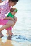 La maman et le bébé sur la plage ont l'amusement Photographie stock