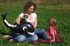 La maman et le descendant jouent sur l'herbe le jour ensoleillé Photos stock