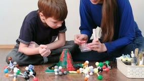 La maman et le fils font l'expérience avec le volcan de pâte à modeler à la maison Réaction chimique avec l'émission de gaz La ma clips vidéos