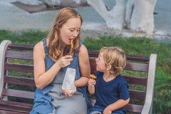 La maman et le fils mangent les patates douces frites en parc Concept de nourriture industrielle Photographie stock