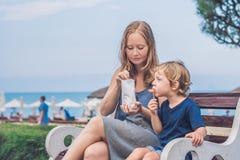 La maman et le fils mangent les patates douces frites en parc Nourriture industrielle concentrée Photos libres de droits