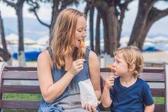 La maman et le fils mangent les patates douces frites en parc Nourriture industrielle concentrée Image libre de droits