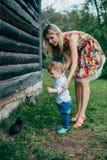 La maman et le fils regardent les chatons Image stock
