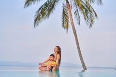 La maman et le fils s'asseyent au bord de la piscine en position de lotus images libres de droits
