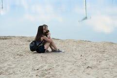 La maman et le fils se reposent sur le sable près du lac Photographie stock