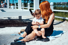 La maman et le fils se reposent sur le sable près du lac Photos libres de droits