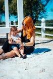 La maman et le fils se reposent sur le sable près du lac Image stock